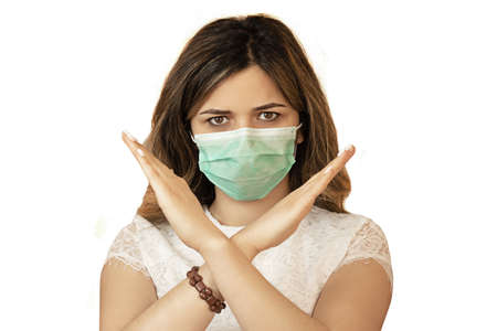 Stop the virus and epidemic diseases. Healthy woman in blue medical protective mask showing gesture stop. Standard-Bild