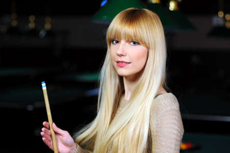 portrait of a beautiful young blonde playing snooker  billiards  photo