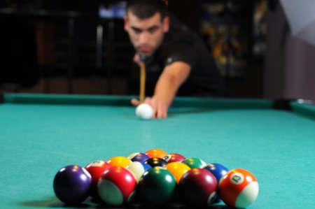billiards room: Man playing snooker in the dark club