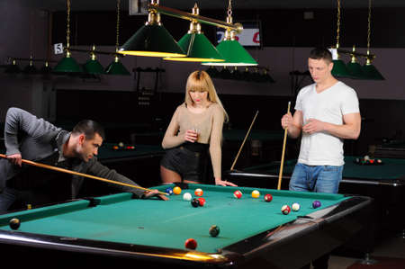 Young attractive people aim at game at billiards photo