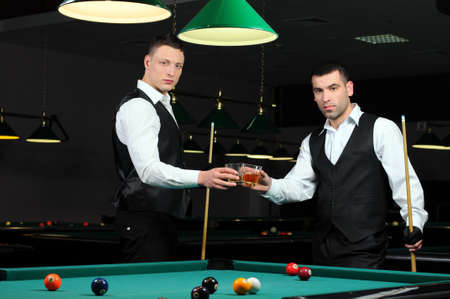 Young people with drinks in their hands to play snooker at the club photo