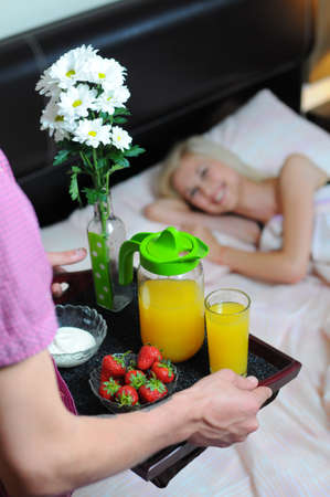 Man bringing the breakfast to his wife in bed photo
