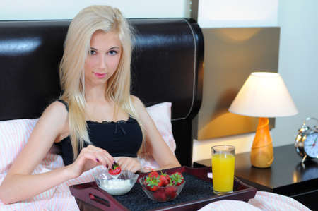 Young beautiful woman having breakfast in bed  photo