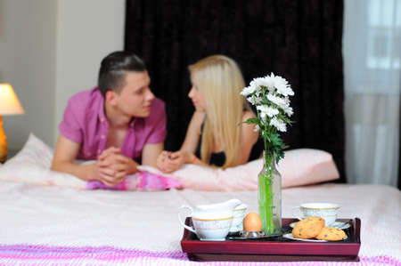 Smiling young couple together getting ready to enjoy breakfast in bed photo