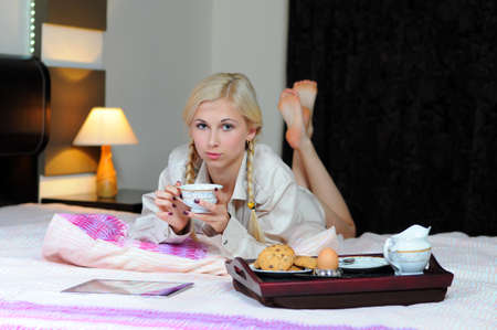 Young red woman in bed having breakfast with tablet pc photo