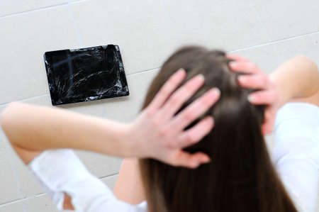 overwrought: young business girl broke the tablet Stock Photo