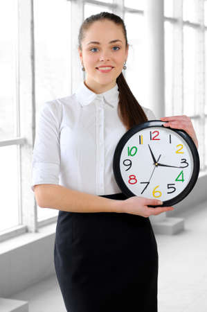 sexy office girl: portrait of a young business girl with a clock in the office