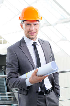 Young engineer with paper plans photo