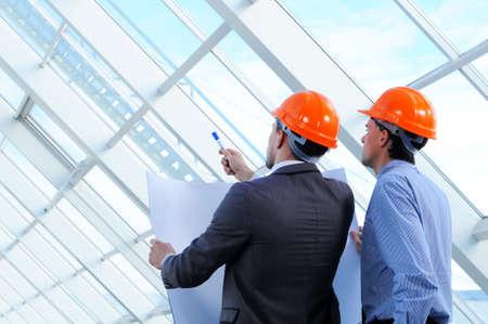 arquitecto: Dos hombres en cascos en sitio de construcci?n