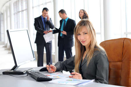 relaxed business man: Pretty Caucasian business woman at office desk with colleagues in the back