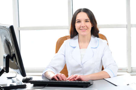 Portrait of young female doctor working in office, sitting at desk doing paperwork, looking at camera, smiling  photo