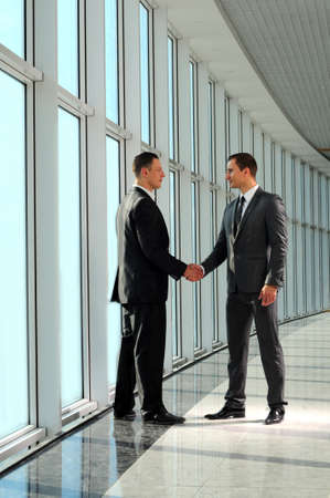 business partner: Cheerful businesspeople, or businessman and client, handshaking Stock Photo