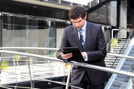 Man using electronic tablet in front of modern building photo