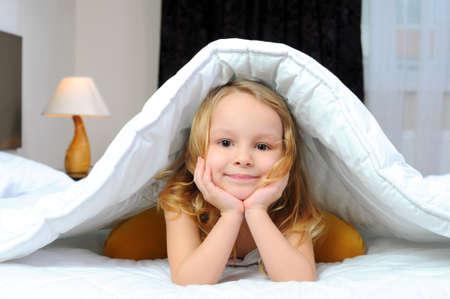 kind met een deken op het bed Stockfoto