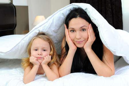 niÑos hablando: Madre y ni?a bajo el edred?n tener tiempo de calidad juntos