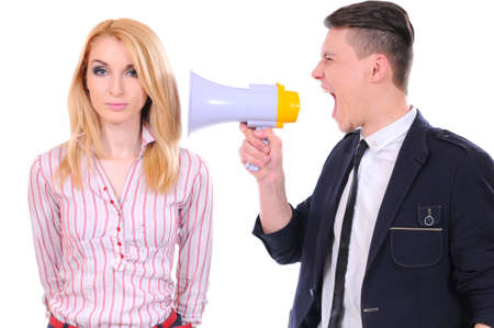 An angry businessman yelling via megaphone to a scared businesswoman isolated on white background photo