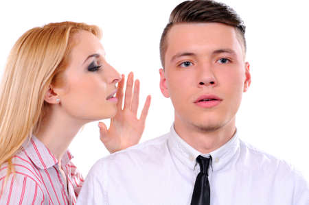 Portrait of young woman telling a secret to a man over a white background photo