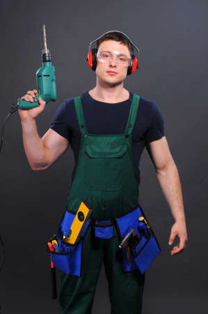 Handsome man with hand drill  black background photo