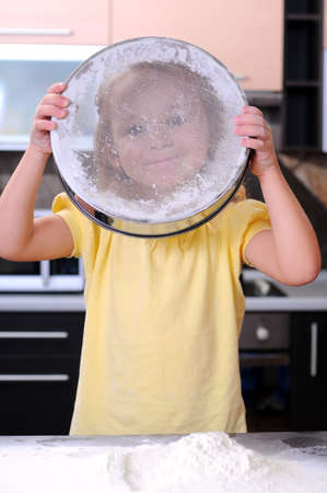 Cute blond little girl making bread in the kitchen photo