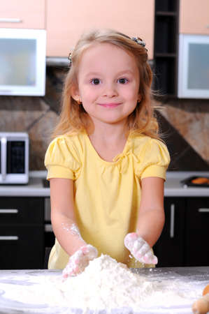 making bread: Carino bambina bionda fare il pane in cucina Archivio Fotografico
