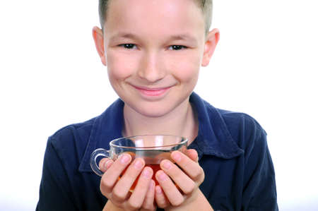 Boy drinking tea isolated on white photo