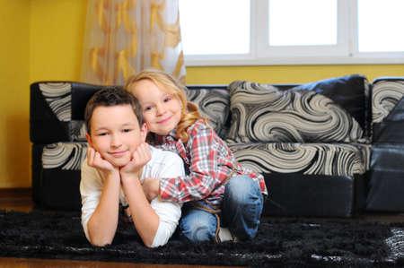 Jolly siblings lying on the floor photo