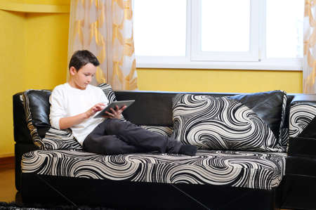 websurfing: Little boy sitting in sofa with electronic tablet