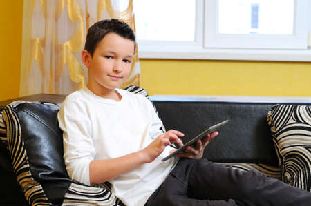 8 10 years: Little boy sitting in sofa with electronic tablet