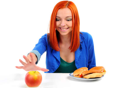 Portrait of pretty young girl deciding what to eat  an apple or hamburger photo