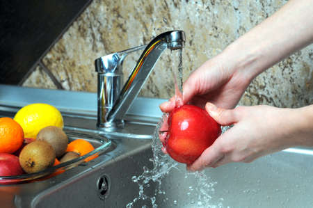 food hygiene: Women wash the apples in the kitchen  Stock Photo