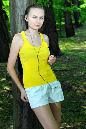 Young woman with mp3 player doing fitness in city park Stock Photo - 20818464