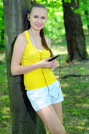 Young woman with mp3 player doing fitness in city park Stock Photo - 20818491