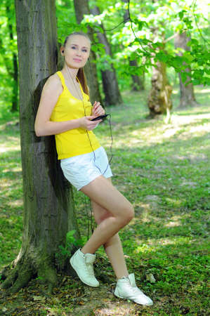 Young woman with mp3 player doing fitness in city park Stock Photo - 20818492