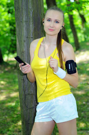 Young woman with mp3 player doing fitness in city park Stock Photo - 20818493