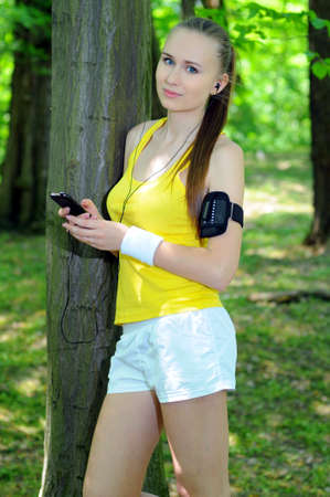 Young woman with mp3 player doing fitness in city park photo