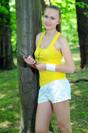 Young woman with tablet doing fitness in city park photo
