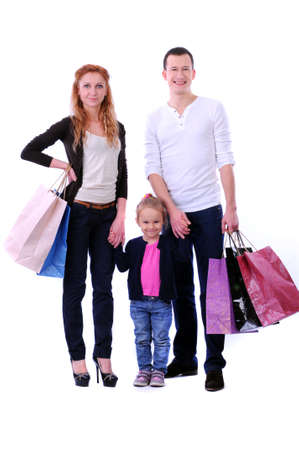 Parents with a child with shopping on white background photo