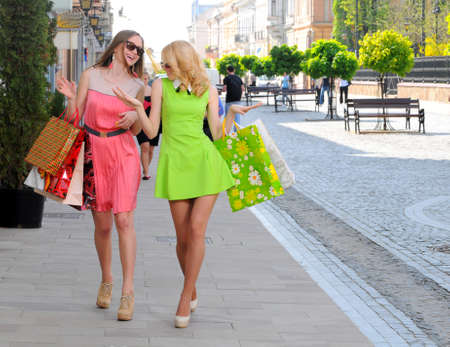 two young women with shopping bags walking in the city photo