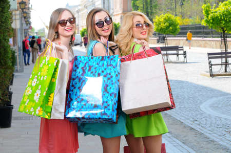 three young women with shopping bags walking in the city photo