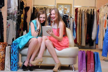 chicas de compras: Las mujeres j?venes con bolsa de la compra con tableta digital Foto de archivo