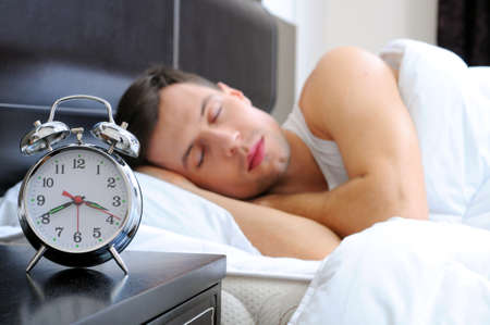 Man sleeping with alarm clock in foreground photo