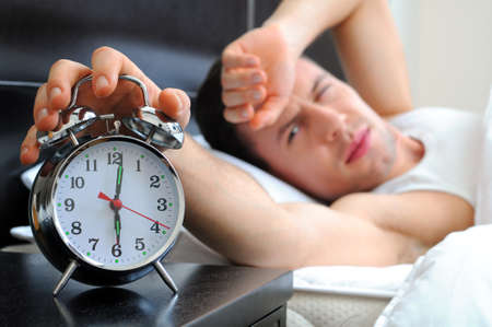 early morning: Man sleeping with alarm clock in foreground Stock Photo