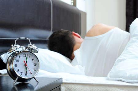 sono: Homem que dorme com despertador em primeiro plano
