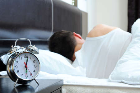 alarm clock: Man sleeping with alarm clock in foreground Stock Photo