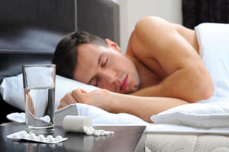 Man sleeping - pills on bed table photo
