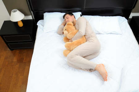 wellness sleepy: portrait of a young man sleeping on the bed embracing his soft toy Stock Photo