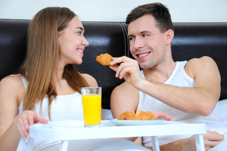 Cheerful young couple having breakfast in bed, relaxing morning photo