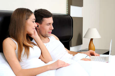 Happy couple with laptop in bed watching fun movie on computer in bed before sleeping  photo