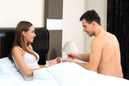 man gives a woman a coffee in bed photo