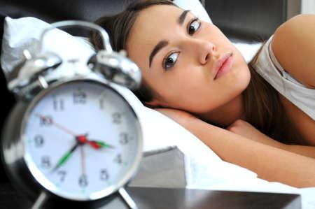 insomnia: Clock with sleep at night  Woman can not sleep  Stock Photo